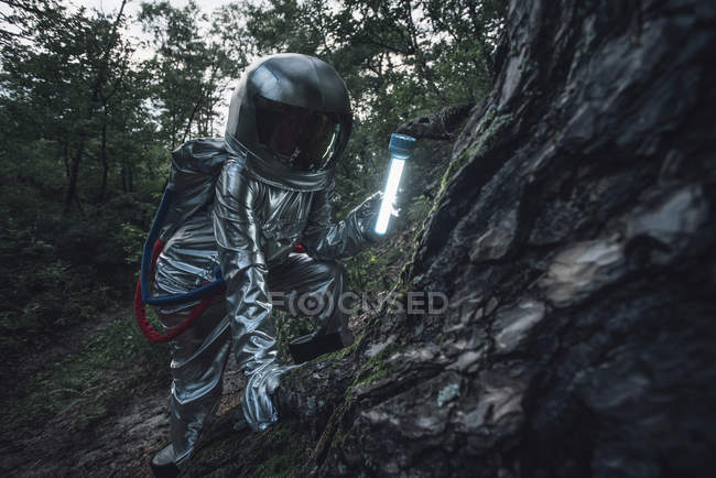 Spaceman exploring nature, using torch in dark forest — Stock Photo