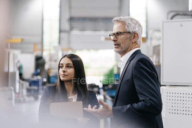 Uomo d'affari e donna d'affari nell'impresa high-tech, avendo un incontro in officina — Foto stock