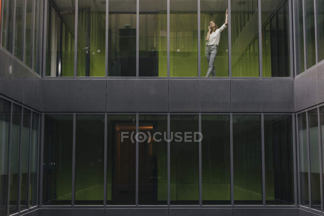 Woman standing at office window, making a phone call — Stock Photo