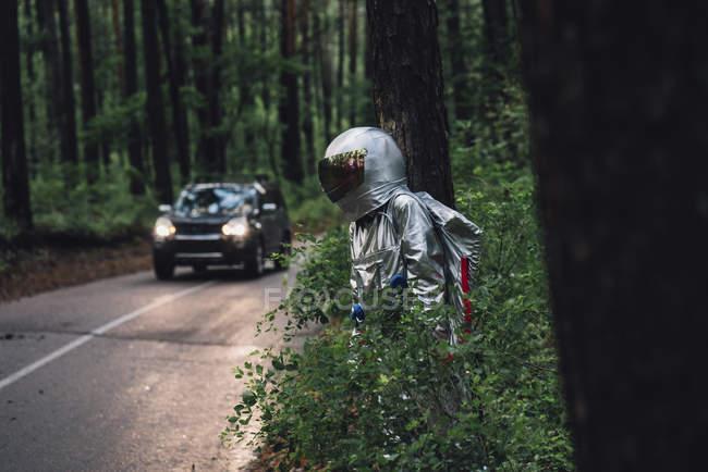 Spaceman que explora a natureza, escondendo na estrada na floresta — Fotografia de Stock