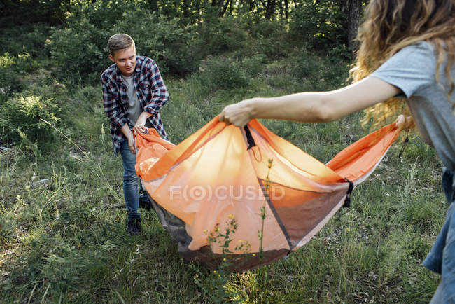 Young couple setting up tent in nature — Stockfoto