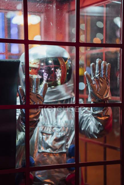 Spaceman emprisonné dans la boîte téléphonique la nuit — Photo de stock