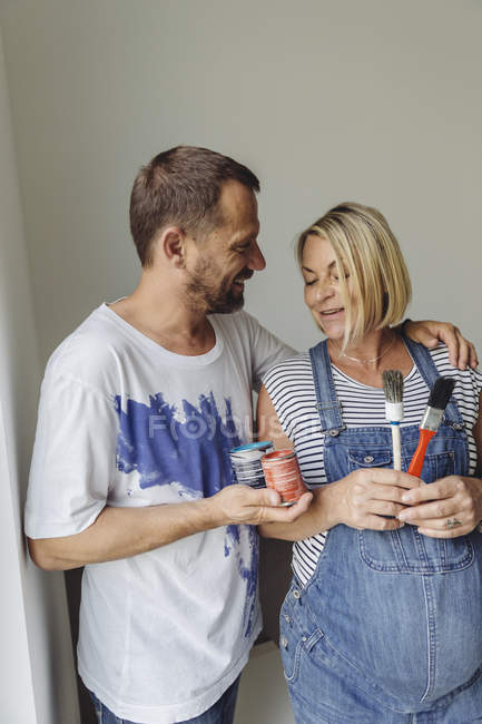 Happy pregnant couple painting home — Stock Photo