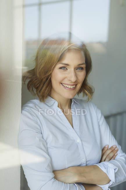 Retrato de una mujer de negocios sonriente detrás del cristal de la ventana - foto de stock