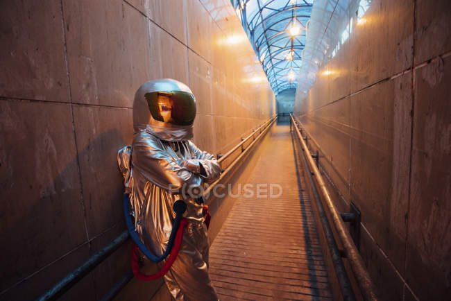 Spaceman in city at night standing in narrow passageway — Stock Photo
