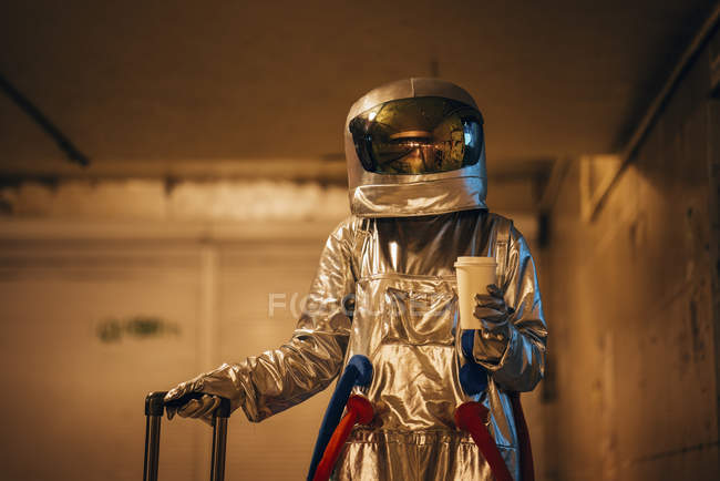 Spaceman in city at night standing in underpass with suitcase and takeaway coffee — Stock Photo
