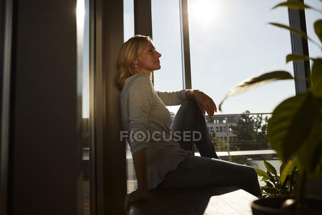 Relaxed mature woman sitting in sunlight at home — Stock Photo
