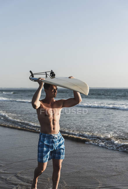 Young man walking on beach, carrying surfboard — Stockfoto