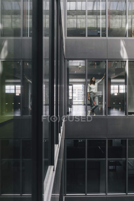 Woman standing at office window and looking up — Stock Photo