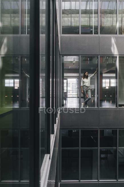 Frau steht am Bürofenster und schaut auf — Stockfoto
