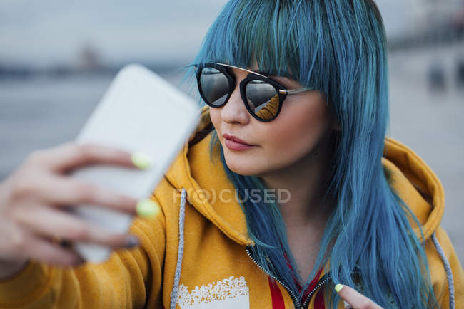 Portrait of young woman with dyed blue hair taking selfie with smartphone — Stock Photo