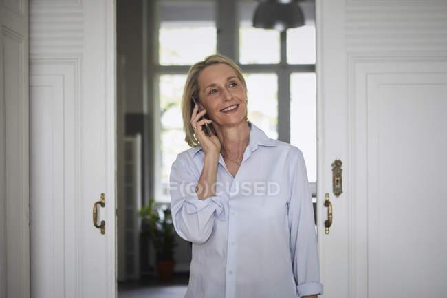 Sorrindo mulher madura no telefone celular em casa — Fotografia de Stock
