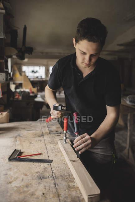 У майстерні тесляр працює над дровами. — стокове фото