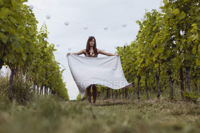 Woman spreading picnic blanket in decorated vineyard — Stockfoto