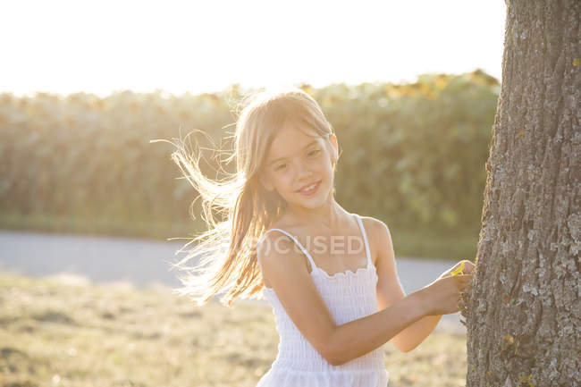 Girl standing on tree trunk at summer evening — Stock Photo