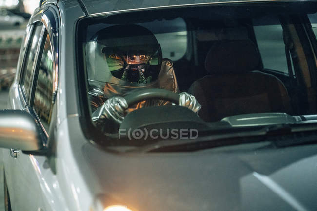 Close-up of spaceman driving car at night — Stock Photo