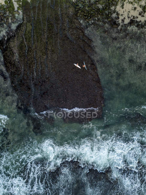 Indonesia, Bali, Aerial view of Bingin beach, two surfers in the ocean — Stock Photo