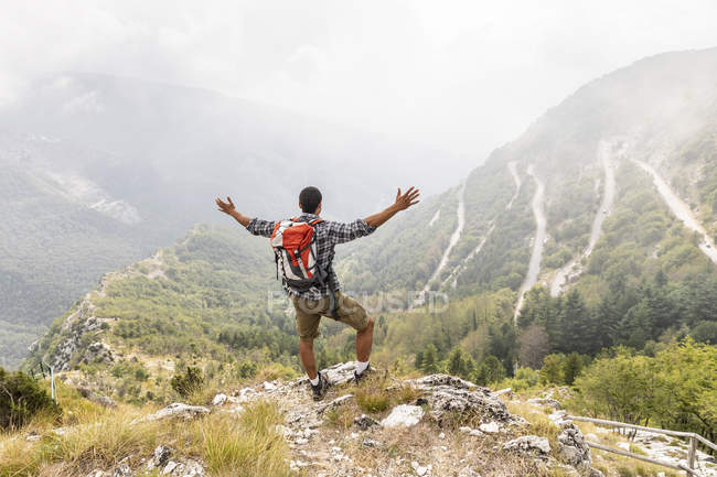 Italy, Massa, man hiking and enjoying the view in the Alpi Apuane — Stock Photo