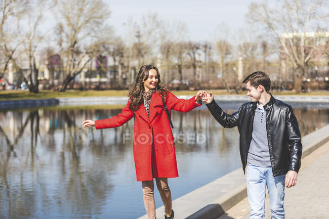 Russia, Moscow, couple dating and having fun at park, young man holding woman 's hand — стоковое фото