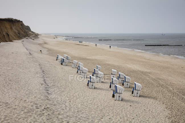 Alemanha, Schleswig-Holstein, Sylt, praia e cadeiras de praia encapuçado vazias — Fotografia de Stock