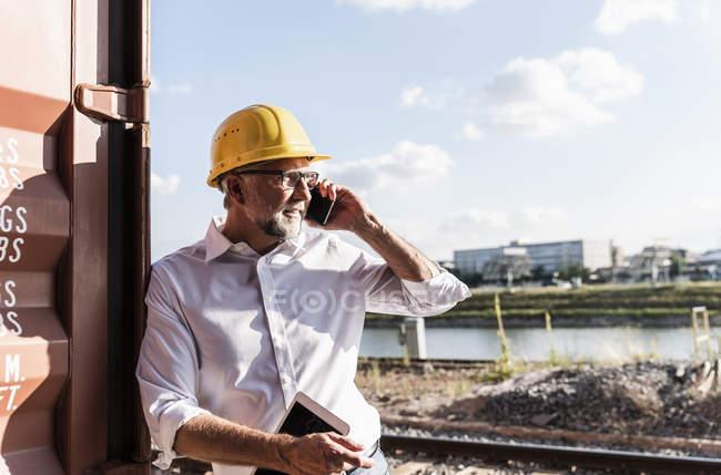 Бизнесмен в грузовой гавани, в защитном шлеме, с помощью смартфона и цифрового планшета — стоковое фото