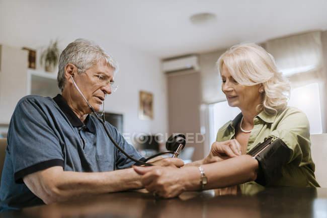 Seniorenpaar nimmt Blutdruck — Stockfoto