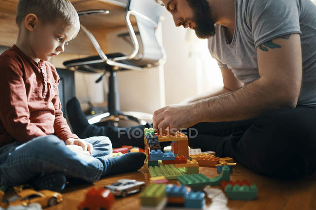 Padre che gioca con i mattoni sul pavimento mentre il suo triste figlioletto lo guarda — Foto stock