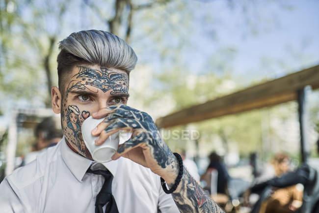 Молодой бизнесмен с татуированным лицом, пьющий кофе — стоковое фото