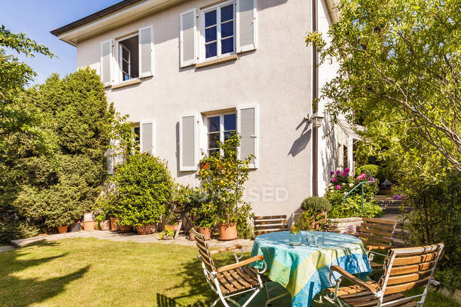Germany, Stuttgart, one-family house, garden table with lawn chairs — Stock Photo