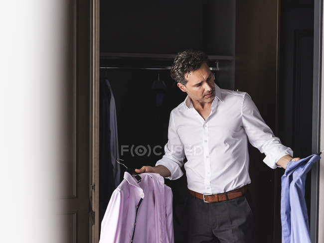 Businessman at home getting dressed choosing shirt from wardrobe — Stock Photo
