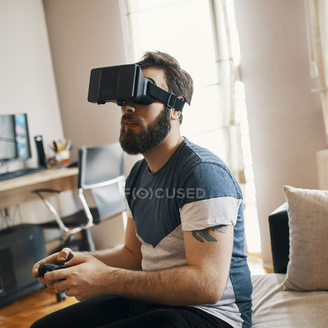 Man wearing virtual reality glasses at home playing computer game — Stock Photo