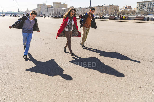 Russia, Moscow, group of friends having fun together and projecting airplane shaped shadows on the ground — Stock Photo