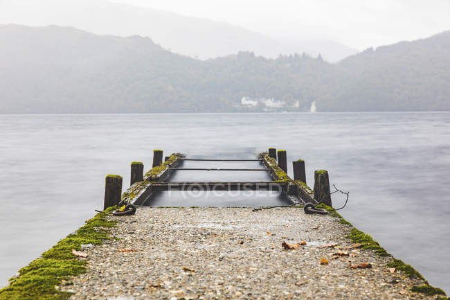 UK, Scotland, wreck of a pier going into a lake in the highlands — Stock Photo