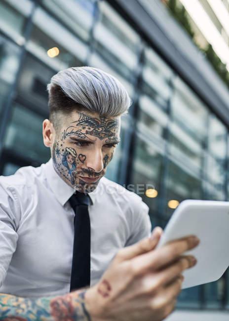 Joven hombre de negocios con cara tatuada, usando tableta digital - foto de stock