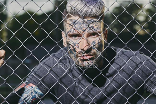 Портрет татуированного молодого человека за оградой — стоковое фото