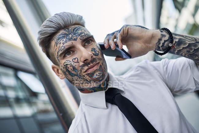 Молодий бізнесмен з татуюванням обличчям, говорячи по телефону — стокове фото