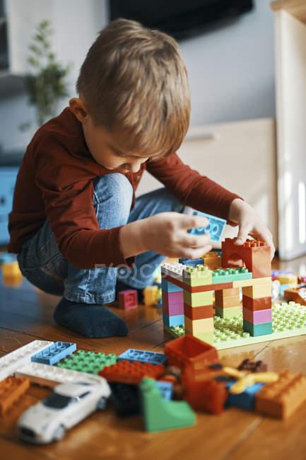 Ragazzino che gioca con mattoni da costruzione sul pavimento a casa — Foto stock