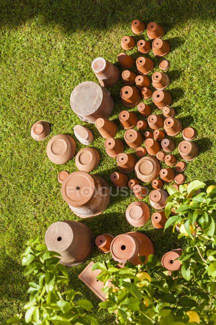 Пустые цветочные горшки, стоящие вверх ногами на траве — стоковое фото