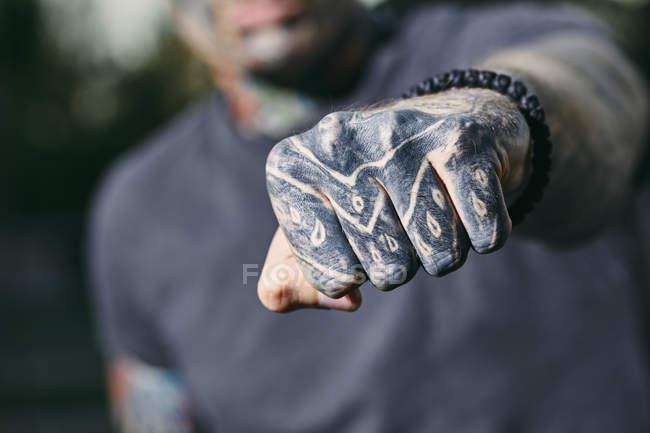 Close-up do punho cerrados do homem novo tattooed ao ar livre — Fotografia de Stock