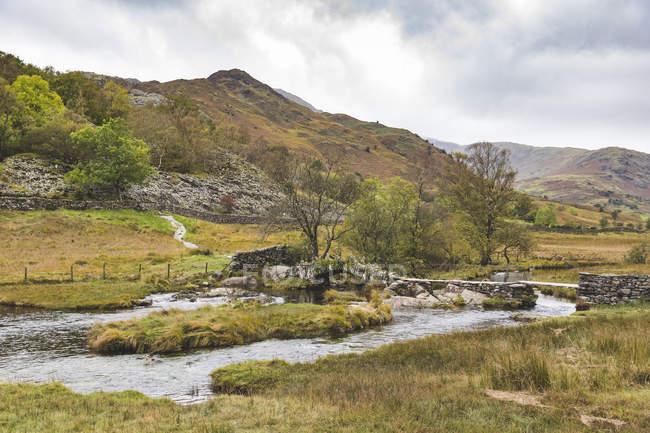 Royaume-Uni, Angleterre, Cumbria, Lake District, Pont de pierre au-dessus de la rivière Brathay — Photo de stock