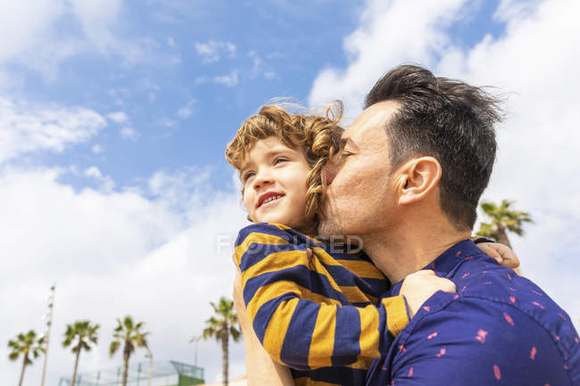 Spain, Barcelona, father kissing son on the beach — Stock Photo