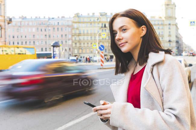 Rússia, São Petersburgo, jovem mulher usando smartphone na cidade — Fotografia de Stock