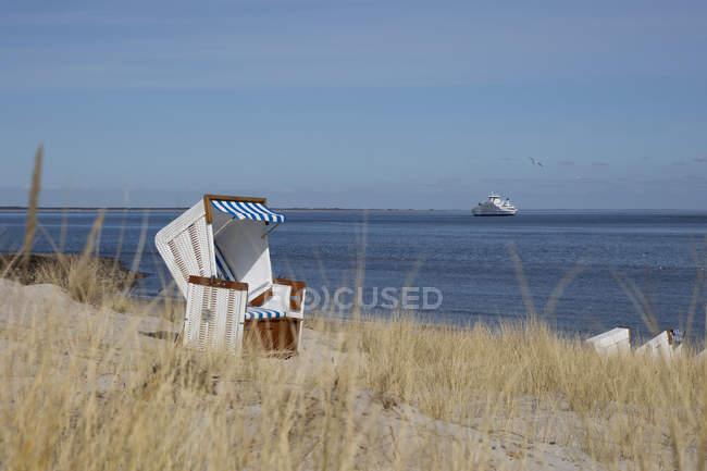 Alemanha, Schleswig-Holstein, Sylt, lista, cadeira de praia encapuçado vazia, navio de cruzeiros no fundo — Fotografia de Stock