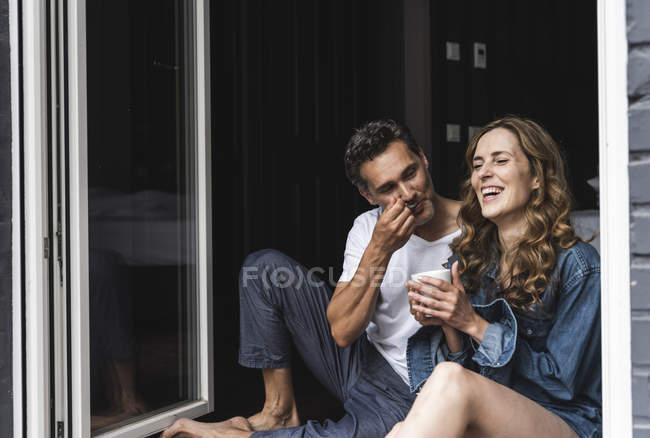 Щаслива пара в нічний одяг вдома, сидячи на французькому вікні — стокове фото