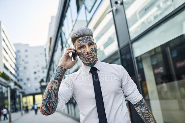 Young businessman with tattooed face, talking on he phone — Stock Photo