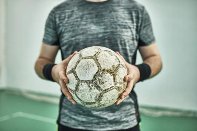 Зблизька футбольний гравець, що тримає м'яч у себе. — стокове фото