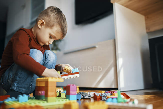Little boy crouching on the floor at home playing with building bricks — Stock Photo