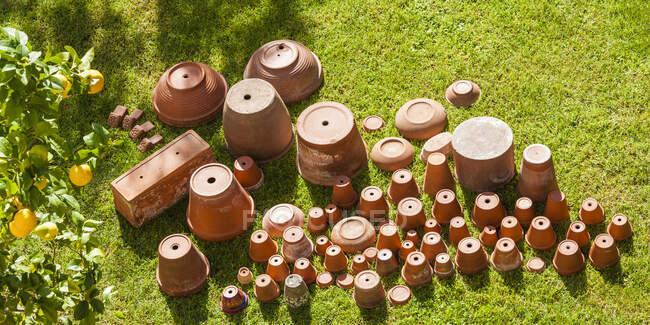 Vasos de flores vazios de cabeça para baixo na grama — Fotografia de Stock