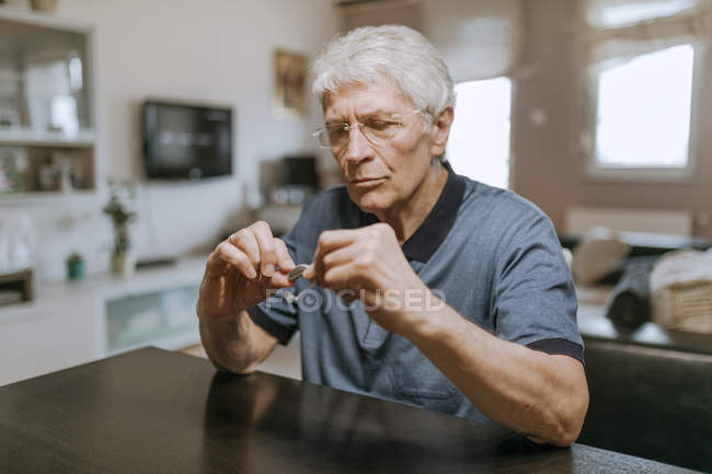 Senior man examining hearing aid — Stock Photo