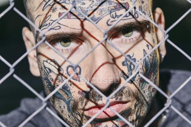 Татуйовані особа молодої людини за паркан — стокове фото